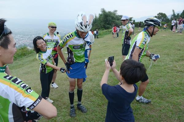 埔里奇單車隊員潘胤杰計畫穿著水手服參加2012年環化自行車大賽,他選在虎頭山上試裝,有小朋友把他當成「偶像」拍照。(柏原祥攝)