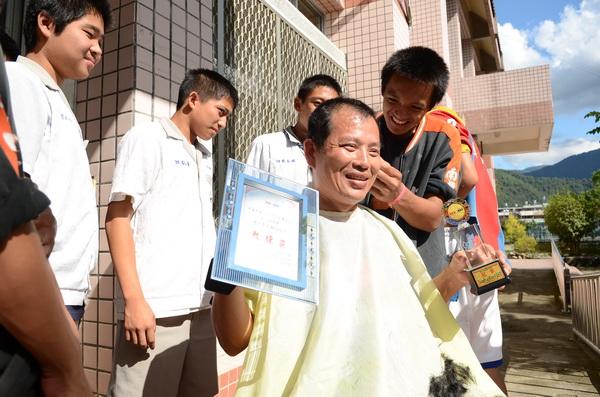 宏中拔河隊教練張金豐實踐諾言讓學生剃頭,過程中他手持獎盃、獎牌,表情複雜。(柏原祥攝)