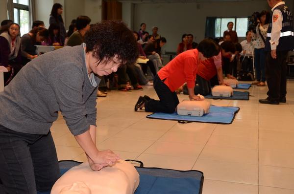 春風關懷協會舉辦全民CPR活動,學員們認真按壓「安妮」,揣摩施力點與力道。(柏原祥攝)