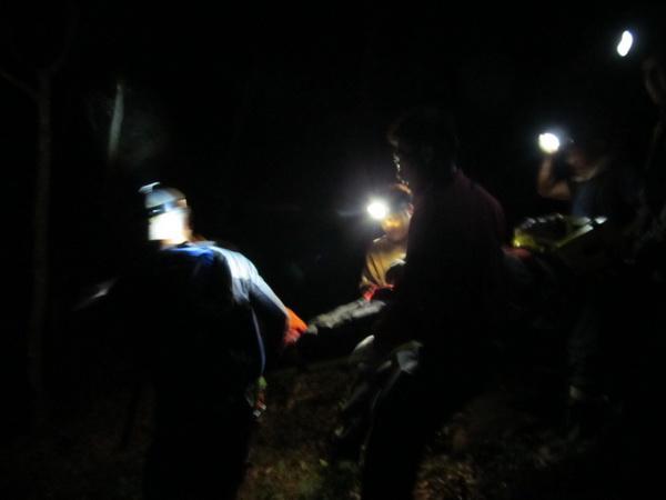 國姓農民爬橄欖樹受傷,救難人員將農民抬上擔架送醫急救。