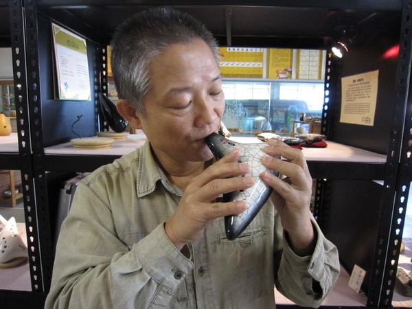 劉鼎魁於鼎記陶坊信手拈來一只黑鑽陶笛,笛音清脆動人。(林子婷攝)