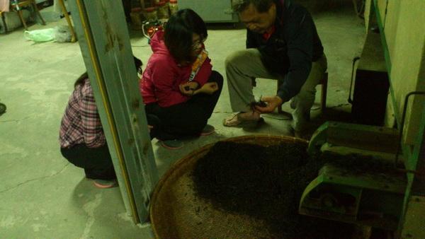於台21線上之私人製茶廠負責人蘇金海(右),正為浪遊學員馮郁筑做解說。(王梓頎提供)