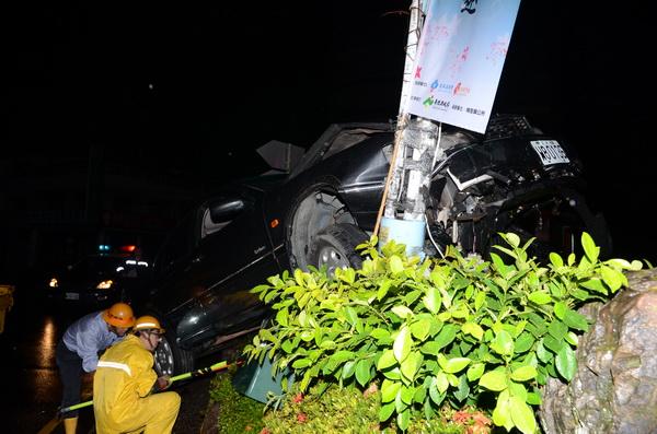 一輛黑色轎車開上仁愛圓環,台電工程人員緊急處置,以免發生危險。(柏原祥攝)