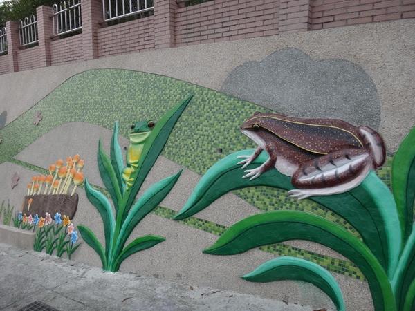 蓮華池位於五城社區,蛙類生態豐富,也成了五城國小藝術牆面的主角。(柏原祥攝)