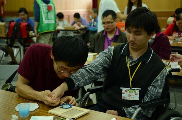 敲敲木工房負責人施文傑(左),握住小腦萎縮症病友周家鈺的手,協助他完成彩繪相框。(柏原祥攝)