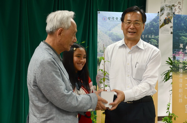 植物學者黃增泉(左)及台電董事長黃重球(右),將台灣大豆種苗交至親愛國小萬大分校學童石葳的手上,象徵復育傳承。(柏原祥攝)