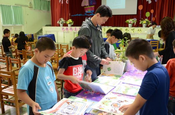 清境國小學童們,翻閱楊景如三姊弟的作品。(柏原祥攝)