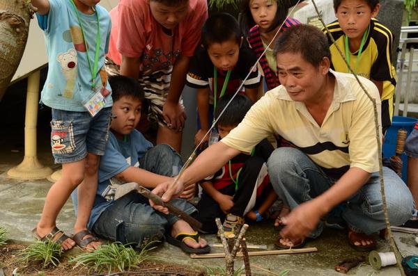 噶哈巫獵人潘志仁(右)在牛眠教會舉辦的夏令營,教導小朋友製作狩獵陷阱。(柏原祥攝)