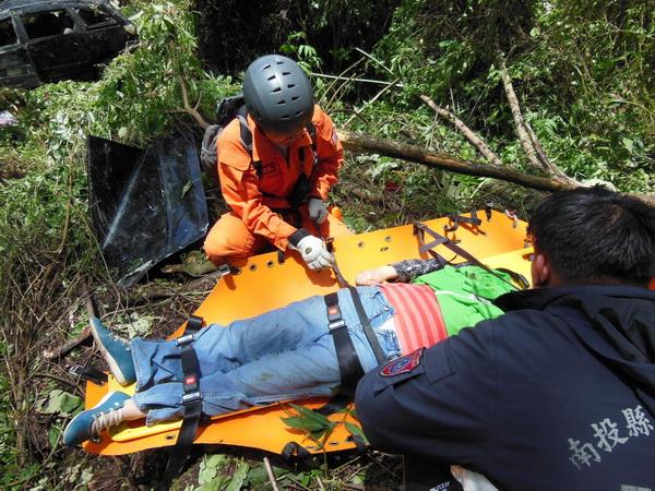 台十四甲線公路鄰近翠峰派出所的路段發生廂型車墜谷的意外,救難人員將傷患固定在長背板上救出。(圖/仁愛消防分隊提供)