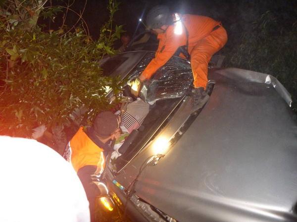 仁愛鄉台14甲線公路轎車撞擊護欄翻車,救難人員破壞車窗將傷者拉出。(圖/仁愛消防分隊提供)