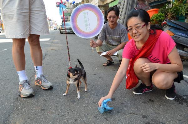可愛狗寵物店老闆娘曾雅萍,在世界無車日走路預演中,示範「遛狗不留便、隨手清狗便」。(柏原祥攝)