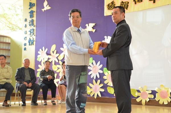 李佩珍老師的家屬將獎助學金交給育英國小校長黃文生(左)代表接受。(柏原祥攝
