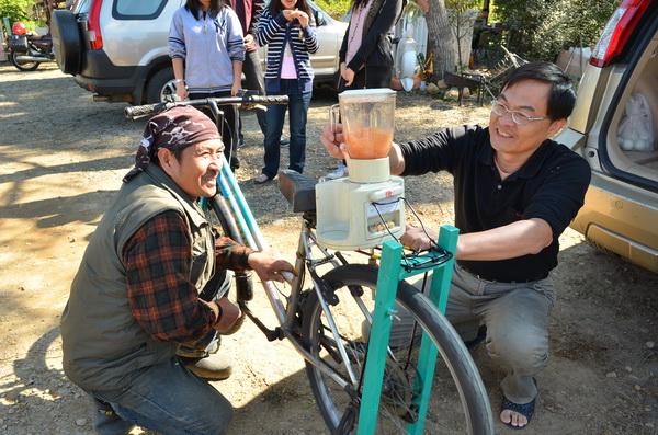 汽修老師袁柏浩(右)設計腳踏果汁機,踩踏即能打出新鮮果汁。(柏原祥攝)