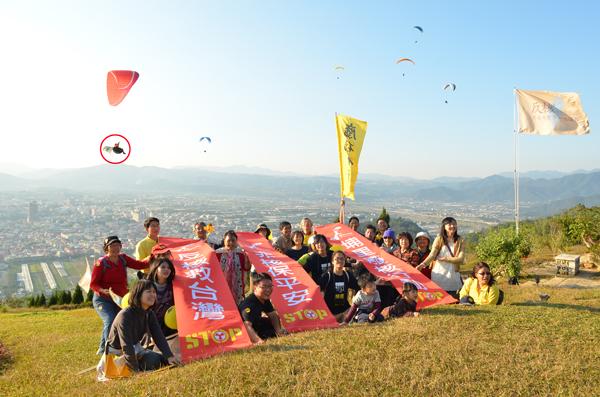 廢核行動聯盟成員在虎頭山拉起旗幟宣揚反核理念,有飛行傘教練(紅圈處)帶反核旗升空聲援。(柏原祥攝)