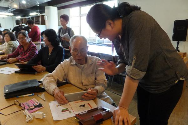 高齡79歲的黃幸夫學平板興致勃勃。(唐茹蘋攝)