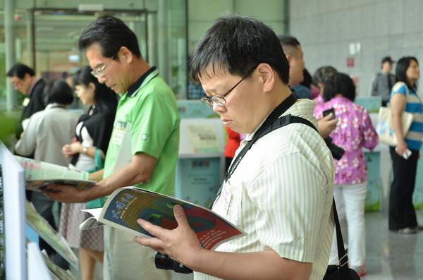 來自台灣各地的社區報工作者拿起《大埔里報》翻閱。(柏原祥攝)