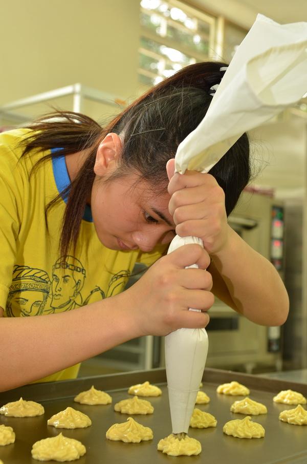 仁愛國中家政烘焙班的同學全神貫注的擠點心餡料。(柏原祥攝)
