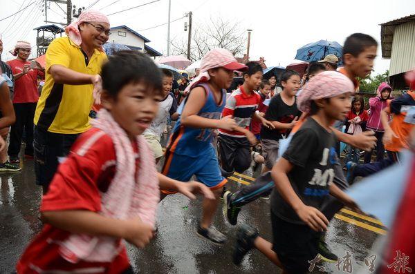 噶哈巫豐年祭熱情登場,小朋友在風雨中奮力走標。(柏原祥攝)