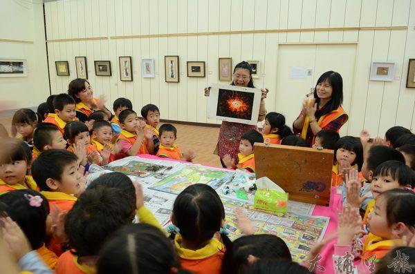 吳翠萍在埔里農會穀倉展出油畫,並教育小朋友現場創作。(柏原祥攝)