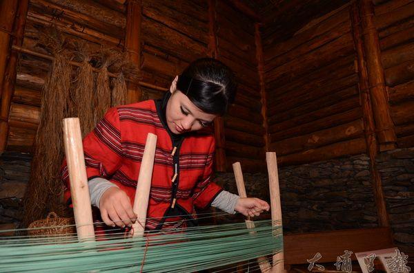 賽德克女子在傳統家屋裡織布。(柏原祥攝)