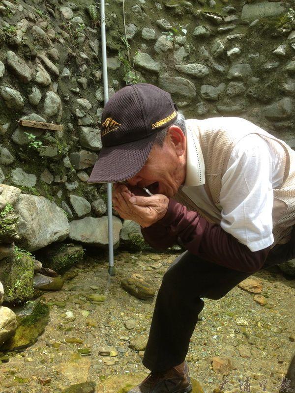 民眾來愛蘭甘泉取午時水,直接取水啜飲,大讚水質絕佳。(里程碑攝)