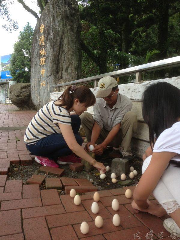 有民眾每年都到埔里地理中心碑立蛋,相傳在此立蛋比較容易成功。(里程碑攝)