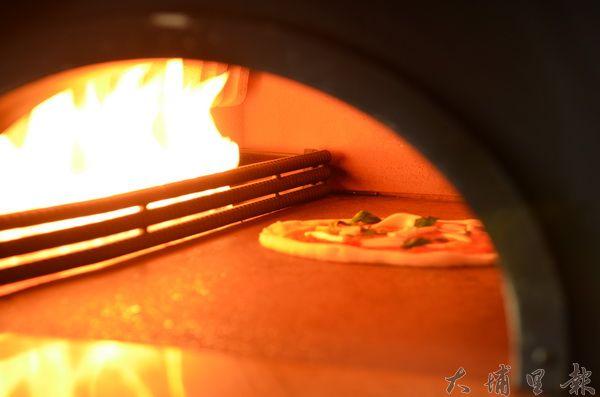 老麵餅皮推進400度的窯烤爐裡瞬間膨脹。(柏原祥攝)