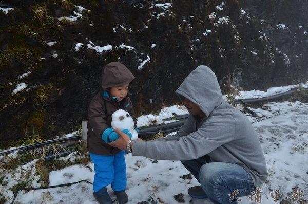合歡山下雪,爸爸帶著小朋友堆雪人。(柏原祥攝)