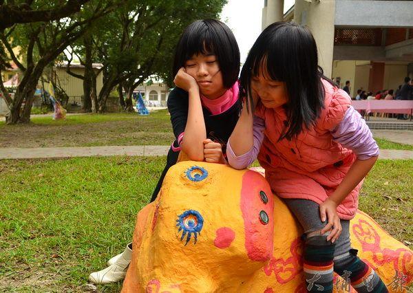忠孝國小小朋友黃于玲、張明華在她們的作品「愛睏牛」上表演打瞌睡。(柏原祥攝)