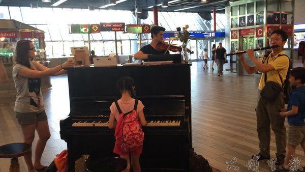 謝志偉帶一家至布拉格旅行,於中央車站中與旅人即興演奏。(圖/謝志偉提供)