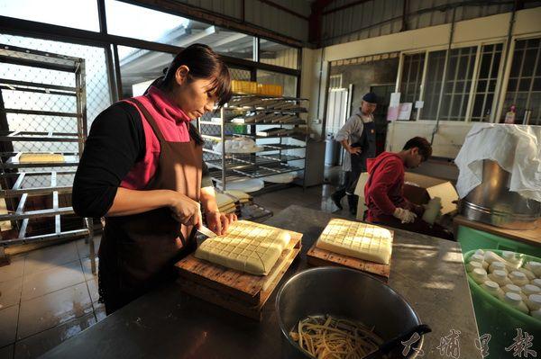 鴻瑞手做豆腐堅持傳統工法,工坊伙伴在晨光中上工,空間瀰漫豆香。(柏原祥攝)