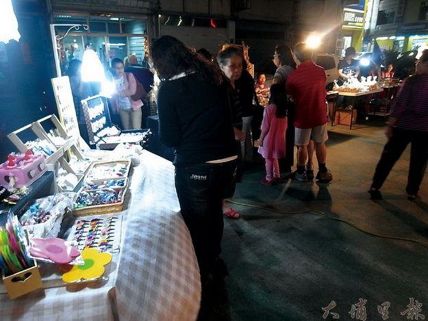 燈光好氣氛佳的市集販售商與顧客,伴以精緻的樂器演奏, 文藝活動帶動買氣!(林子婷攝)