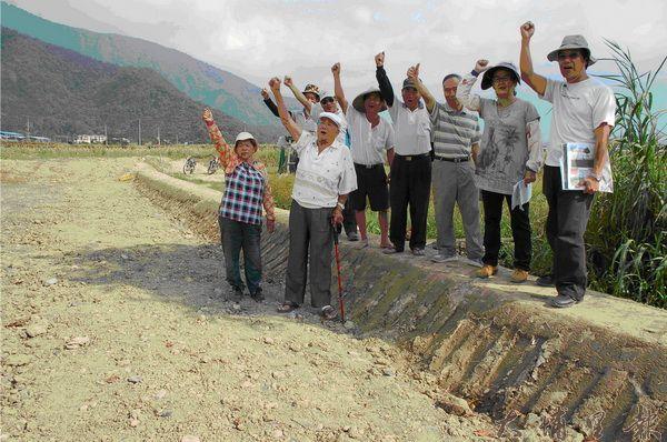 財團整地築堤封路,埔里鎮福興里農民站在土堤上抗議。(柏原祥攝)