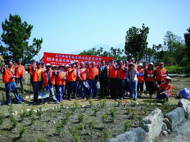 水頭社區居民義務勞動整理塑造一個小三角公園雛型後合影(梁瑞仁攝)。