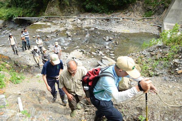 南投林管處官員與蝴蝶保育志工會勘彩蝶瀑布,因步道被沖毀,途中需高繞越過溪水(柏原祥攝)