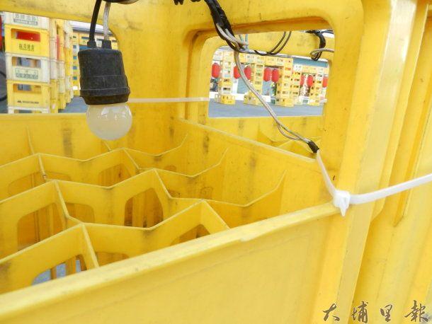 「金蛇納財」花燈以啤酒箱堆疊,接上電線、燈泡,點綴紅色燈籠而成。 (廖堉汝攝)