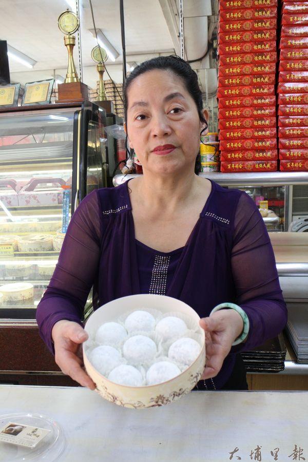 老闆娘陳阿綢手持招牌紅豆麻糬,顆顆渾圓玉潤,令人垂涎。(林子婷攝)