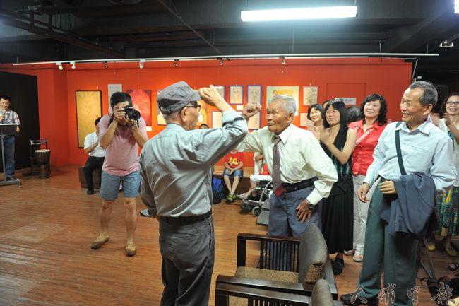 94歲台籍日本兵劉英輝(中)在女兒畫展中與昔日同僚黃金印會面,兩人行軍禮,並唱起了日本軍歌。(柏原祥攝)