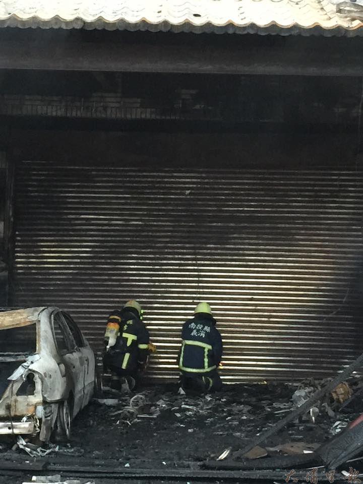 日月潭伊達邵商圈23日凌晨發生大火,6棟民宅店面陷入火海,消防人員撬開鐵捲門入內撲救。(林育正攝)