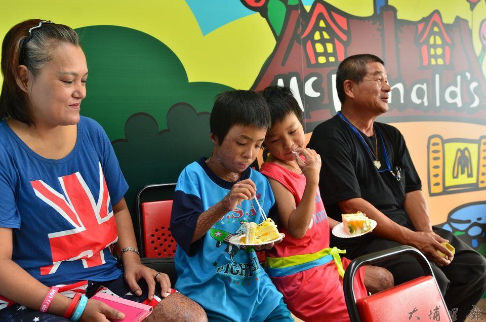 武界部落馬家燒傷姊弟開心地吃著自己重獲新生的蛋糕,父母也露出欣慰的笑容。(柏原祥攝)