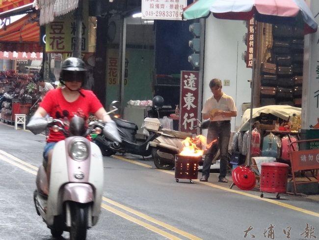 雖然公所大力宣導防制PM2.5空污的重要,但中元普渡時,許多鎮民仍然習慣燒紙錢。(柏原祥攝)