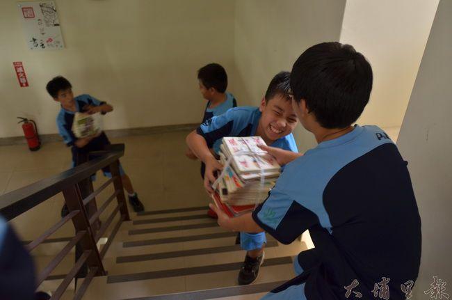 埔里國中同學協力傳書,為埔里圖書館「青春創酷學習中心」貢獻己力。(柏原祥攝)