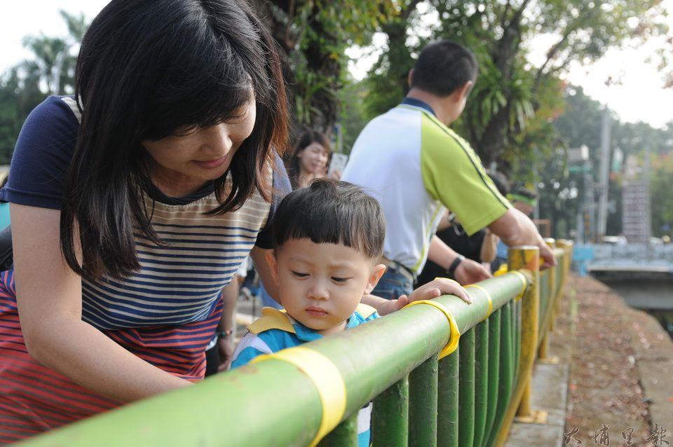 護樹行動的會場,有阿嬤帶著孫子在南安路護岸欄杆上綁上黃絲帶,為161棵即將移植的樹木祈福。(柏原祥攝)