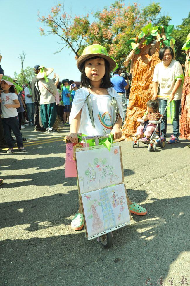 有小朋友帶著樹木的畫作,坐著滑板車,參與埔里護樹大遊行。(柏原祥攝)