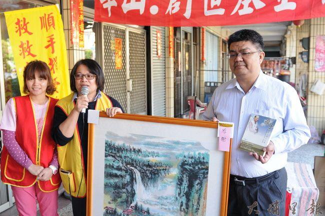 南投出身的企業家崔信基(右),捐款給華山‧創世基金會,基金會社工回贈創辦人畫作與自傳。