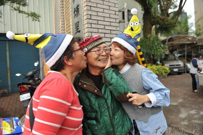 牛耳藝術度假村董事長黃炳松耶誕節準備了一千份火雞肉刈包幫助弱勢家庭,志工答謝他送上熱吻。(柏原祥攝)