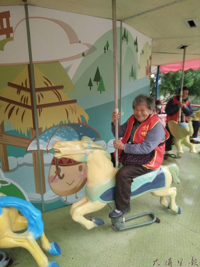 老人在泰雅渡假村騎著旋轉木馬相當開心。(華山基金會提供)