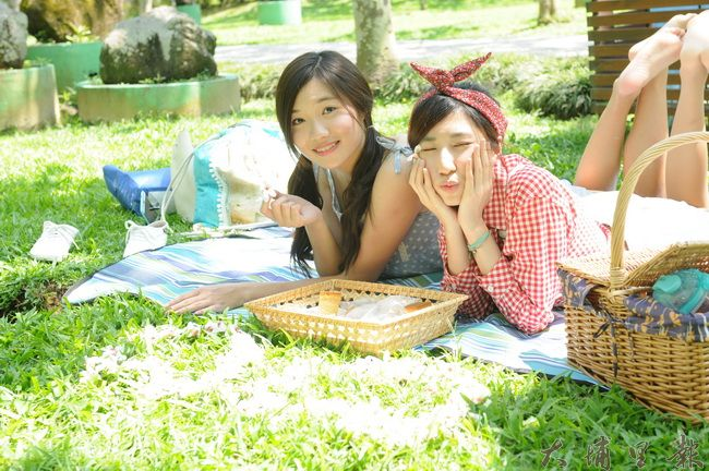 暨大觀餐系同學在草皮上將油桐花鋪成了心型,帶著愉悅的心情野餐。(柏原祥攝)