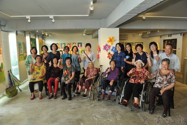 桃米及內加道長青繪畫班的長輩們與指導老師石鈴、廖珮如在畫作前合影。(柏原祥攝)