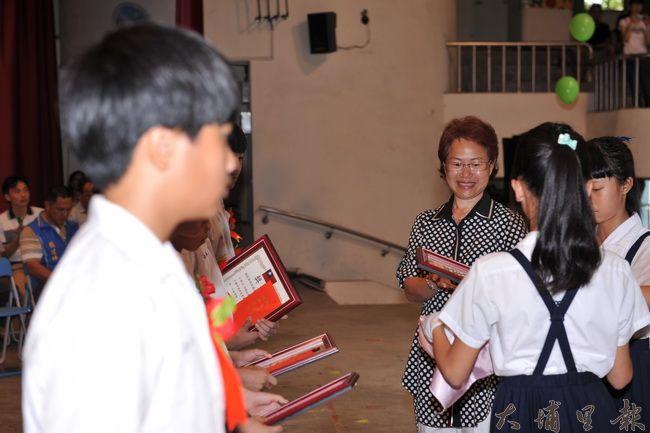 埔里國小跆拳道教練遺孀柯玉秀代表先生,在埔里國小畢業典禮上頒贈黎明體育貢獻獎。(柏原祥攝)
